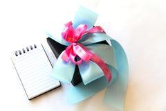 Zwarte giftdoos met blauwe en roze lintboog met blocnote Stock Afbeeldingen