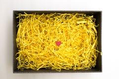 Zwarte giftdoos met geel verpakkingsmateriaal en rode hartwijze Stock Foto's