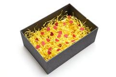 Zwarte giftdoos met geel verpakkingsmateriaal en rode hartwijze Stock Fotografie