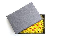 Zwarte giftdoos met geel verpakkingsmateriaal en rode hartwijze Stock Afbeeldingen