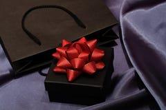 Zwarte giftdoos met zwarte het winkelen zak op donkere stof stock afbeeldingen