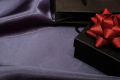Zwarte giftdoos met zwarte het winkelen zak op donkere stof royalty-vrije stock afbeeldingen
