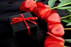 Zwarte giftdoos met rood lint dichtbij rode tulp Stock Fotografie