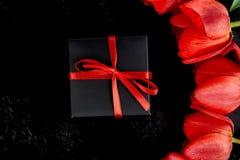 Zwarte giftdoos met rood lint dichtbij rode tulp Stock Foto