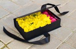 Zwarte giftdoos met zonnebloemen en heldere Franse zoete roze maca Royalty-vrije Stock Afbeelding