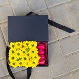 Zwarte giftdoos met zonnebloemen en heldere Franse zoete roze maca Stock Afbeeldingen