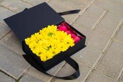 Zwarte giftdoos met zonnebloemen en heldere Franse zoete roze maca Stock Afbeelding