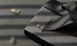 Zwarte giftdoos op een donkere tegenover elkaar gestelde die achtergrond, met a wordt verfraaid Royalty-vrije Stock Fotografie