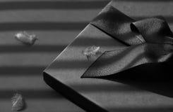 Zwarte giftdoos op een donkere tegenover elkaar gestelde die achtergrond, met a wordt verfraaid Stock Afbeelding