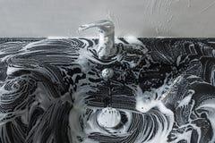 Zwarte glasgootsteen in zeepschuim Het schoonmaken van de gootsteen Conceptenhou Royalty-vrije Stock Fotografie