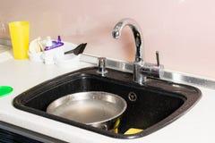Zwarte gootsteen met afwasmachine en gele spons Royalty-vrije Stock Afbeeldingen