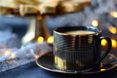 Zwarte gouden koffiekop met een schotel van koekjes en lichten op de achtergrond stock afbeeldingen
