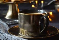 Zwarte gouden koffiekop met een schotel van koekjes en ster bokeh op de achtergrond royalty-vrije stock fotografie