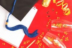 Zwarte graduatie GLB met blauw lint op rood stock afbeeldingen