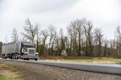 Zwarte grote installatie klassieke semi vrachtwagen met aangezette koplamp die commerciële lading in bulk semi aanhangwagen verv royalty-vrije stock fotografie