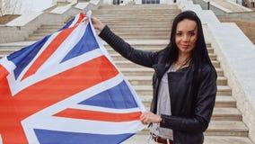 Zwarte haired vrouwenholding in handenunie Jack Flag Waving On Wind stock footage