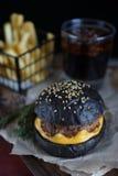 Zwarte hamburger op ambachtdocument stock afbeeldingen
