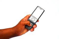 Zwarte hand die mobiele telefoon met behulp van Stock Fotografie