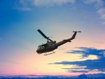 Zwarte helikopter die in aardige zonsondergang met rode en gele blauwe hemel op berg en boomhout vliegen stock afbeelding
