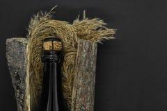 Zwarte het glasfles van Champagne die in boomschors wordt geplaatst met neiging op zwarte achtergrond stock fotografie