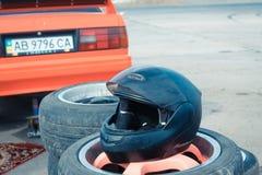 Zwarte het rennen helm die op een stapel van gebruikte banden bij Vinnytsia-Afwijkingsconcurrentie 09 rusten 07 2017, redactiefot Royalty-vrije Stock Fotografie