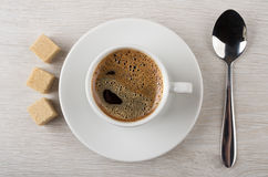 Zwarte hete koffie in kop, bruine klonterige suiker en lepel Stock Foto