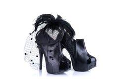 Zwarte hoge hiel vrouwelijke schoenen en fascinator van het veerhaar stock afbeelding