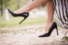 Zwarte hoge hielen op de voeten van een jonge vrouw stock afbeeldingen