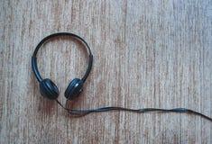 Zwarte hoofdtelefoon met rustieke achtergrond stock afbeeldingen
