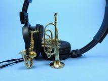 Zwarte hoofdtelefoons, een saxofoon en een trompet De muzikale instrumenten zijn miniaturen royalty-vrije stock fotografie