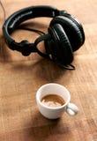 Zwarte hoofdtelefoons en een kop van koffie op rustieke houten achtergrond stock afbeeldingen
