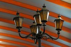 Zwarte ijzerpool met lantaarns en lampen onder een gestreept plafond stock foto