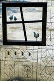 Zwarte ijzervogel op een raamkozijn in een mooie tuin in heldere dagen stock afbeelding
