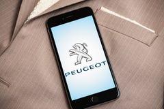 Zwarte iPhone met embleem van Franse autofabriek Peugeot op het scherm royalty-vrije stock afbeelding