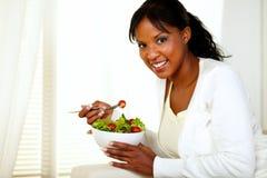 Zwarte jonge vrouw die een groene salade eet stock foto's