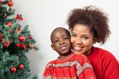 Zwarte jongen met zijn moeder dichtbij de boom Stock Foto