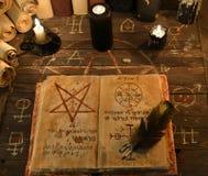 Zwarte kaarsen en open magisch boek met pentagram Stock Foto's
