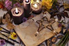 Zwarte kaarsen en pentagram op heksenlijst royalty-vrije stock afbeelding