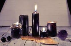 Zwarte kaarsen, oud perkament en magische bal tegen witte plankenachtergrond Royalty-vrije Stock Fotografie