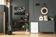 Zwarte kaart op grijze muur in donker woonkamerbinnenland met installaties stock foto's