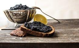 Zwarte kaviaar in een zilveren kom met brood en citroen op een houten achtergrond Royalty-vrije Stock Afbeelding