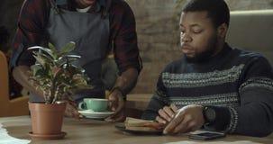 Zwarte kelner die een mensenkoffie en verfrissingen dienen Stock Afbeeldingen
