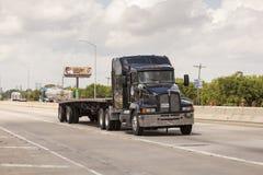 Zwarte Kenworth-Vrachtwagen op de weg stock afbeelding