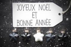 Zwarte Kerstmisballen, Sneeuwvlokken, de Middelen Gelukkig Nieuwjaar van Bonne Annee Stock Foto's
