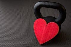 Zwarte kettlebell op een zwarte gymnastiekvloer met groot rood hart royalty-vrije stock fotografie
