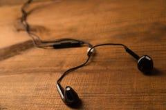Zwarte kleine hoofdtelefoons op een houten geïsoleerde achtergrond Horizontaal kader Royalty-vrije Stock Foto's