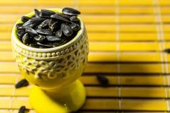 Zwarte kleine zonnebloemzaden Klik zaden met schillen Een handvol in een gele miniatuurtribune op een houten servet Morste sommig royalty-vrije stock afbeelding
