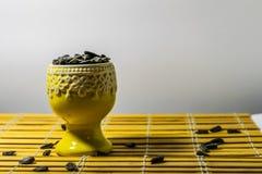 Zwarte kleine zonnebloemzaden Klik zaden met schillen Een handvol in een gele miniatuurtribune op een houten servet Morste sommig stock afbeeldingen