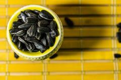 Zwarte kleine zonnebloemzaden Klik zaden met schillen Een handvol in een gele miniatuurtribune op een houten servet Morste sommig royalty-vrije stock afbeeldingen