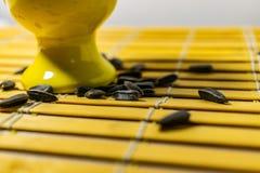 Zwarte kleine zonnebloemzaden Klik zaden met schillen Een handvol in een gele miniatuurtribune op een houten servet Morste sommig royalty-vrije stock fotografie